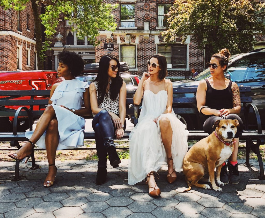 Group of women sitting on park bench with dog