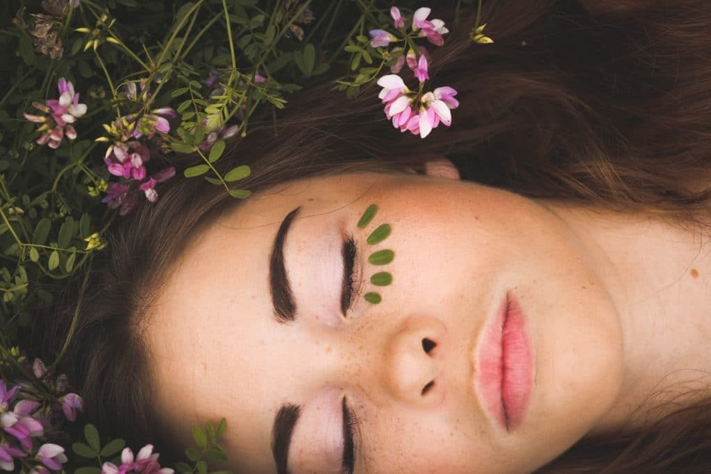 woman eyes closed next to flowers
