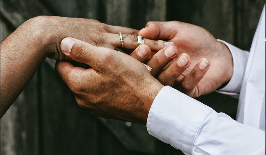 Groom putting on wedding ring