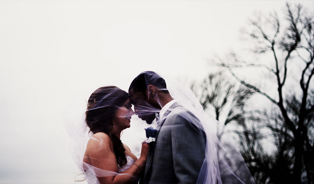 Bride and groom under veil outdoors