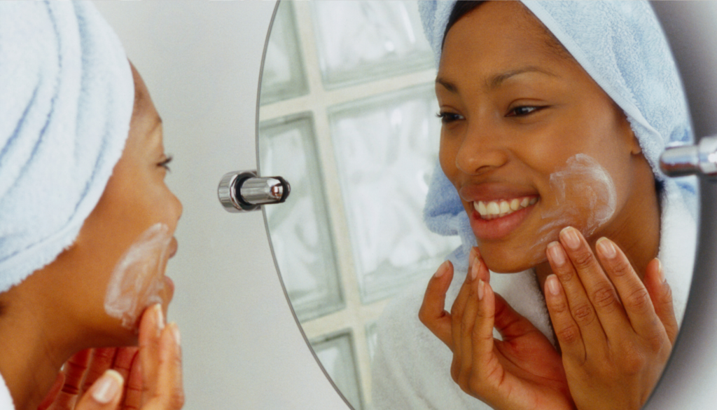 woman looking into mirror cleansing skin