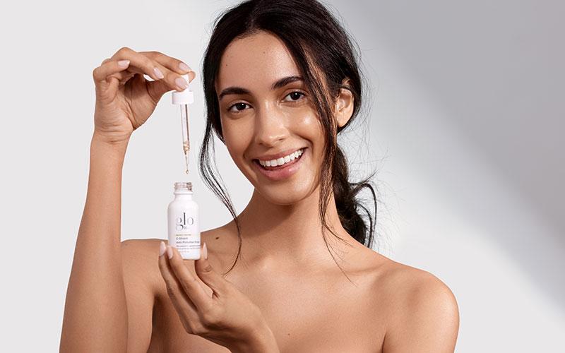woman holding glo skin beauty serum