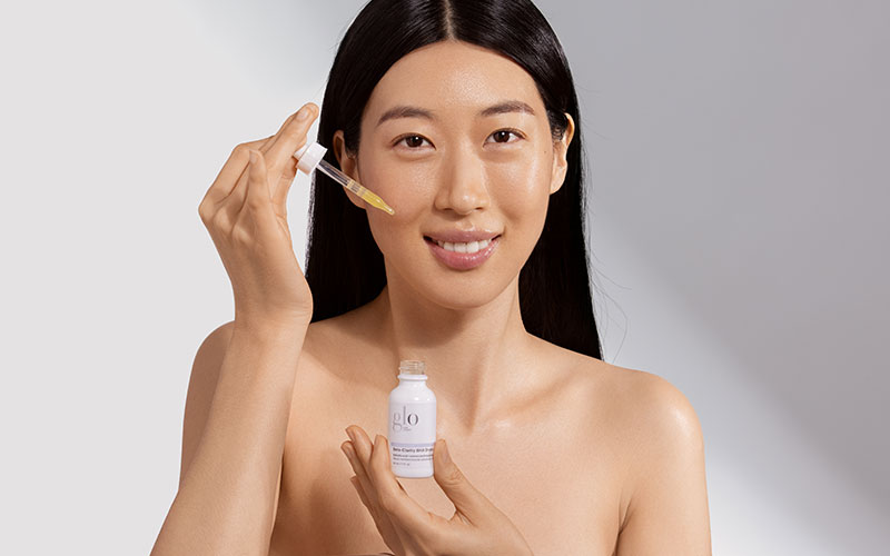 woman holding glo beauty acne product